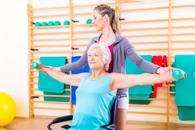 Young Lady assisting elderly woman doing yoga